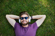 Happy man listening to music while lying on the grass outdoors and wearing sunglasses