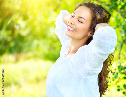 Beautiful young woman enjoying nature outdoor. Happy smiling brunette girl relaxing in the summer park, healthcare concept