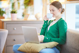 Young woman working at home with laptop and coffee