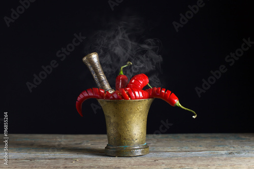 Fotobehang Hot chili peppers Red chili pepper in old copper mortar.