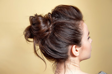 Rear view of female hairstyle middle bun with brown hair. © Viktoria
