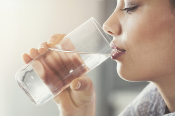 Young woman drinking pure glass of water
