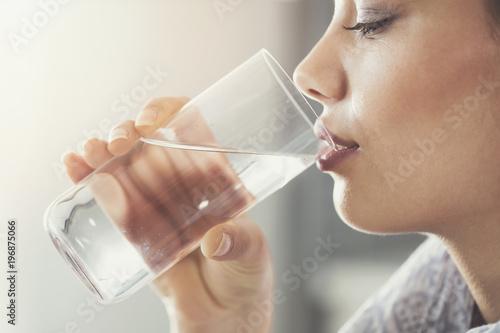 Młoda kobieta pije czystą szklankę wody