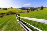 haystack behind the wooden fence on a grassy hill. beautiful Carpathian countryside in springtime. mountain ridge with snowy tops in the distance - 196875628