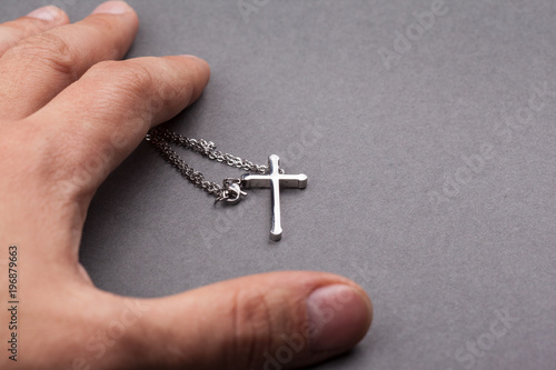 Silver cross in a hand - 196879663