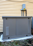 Residential generator on concrete pad, next to a house wall - 196881687