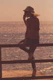 Silhouette of a young girl enjoying the ocean / sea.