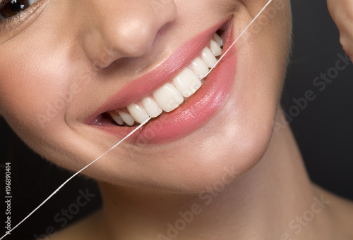 Close up of white healthy teeth of joyful young woman. She is using dental floss. Oral hygiene concept