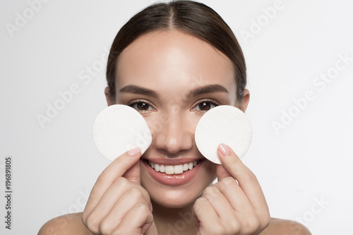 Skincare routine. Portrait of happy cute girl is standing and holding cotton pads. She is looking at camera with joy. Beauty concept and isolated background