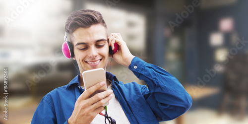 Fototapeta young man with phone and headphones listening to music