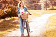 Beautiful girl and bicycle with flowers in basket at park