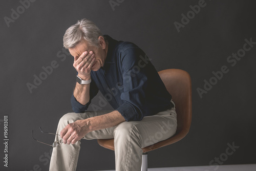 Tired old man closing face by hand while locating on seat. Fatigue during job concept
