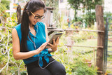 Asian women are using tablets in the garden. - 196904881