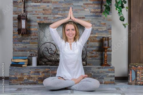Fototapeta Young woman practicing yoga indoors