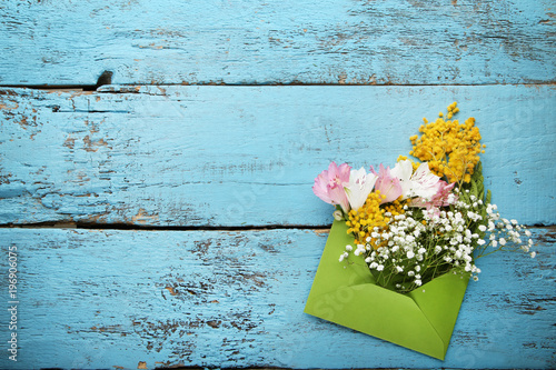 Bouquet of beautiful flowers with envelope on blue wooden table