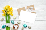 easter greeting card with easter eggs and spring flowers mock up over white wooden table