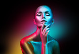 Fashion model woman in colorful bright sparkles and neon lights posing in studio, portrait of beautiful sexy girl. Art design colorful vivid makeup - 196927009