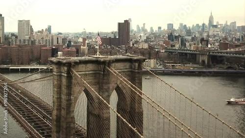 Brooklyn Bridge with American flag - aerial moving toward Manhattan skyline in New York City NYC in 1080 HD