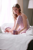 Young beautiful woman sitting in bed with laptop - 196929824