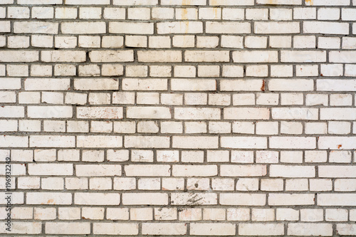 Background of the damaged old brick wall with horizontal masonry