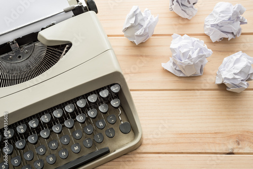 Beżowy typewriter wraz z papierowymi piłkami na drewnianym stole. Widok z góry