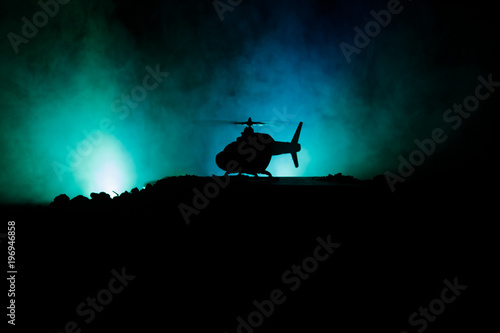Fototapeta Silhouette of military helicopter ready to fly from conflict zone. Decorated night footage with helicopter starting in desert with foggy toned backlit. Selective focus.