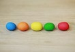 Colorful bright Easter little eggs lined up in the middle of picture, made of plasticine on wooden blurry background with blue, orange, yellow, green and red colors, contrast