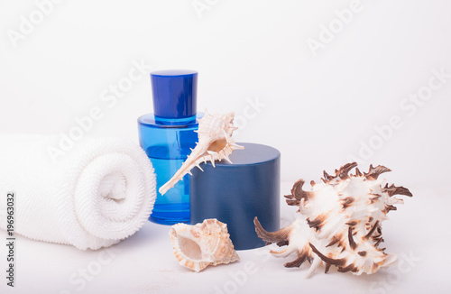 Papiers peints Spa Spa salon concept with rolled white towel, blue bottle and seashells on white wooden background. Spa treatments. Spa background. Space for a text.