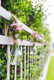 A purple flowers in light bulb shaped vase hanging on home fence. - 196968087