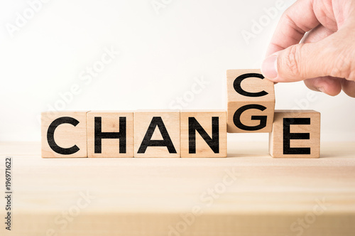 "Business and design concept - surreal abstract geometric wooden cube take by hand with word "" CHANGE & CHANCE "" concept on wood floor and white background"