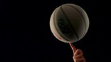 spinning a basketball in front of a black studio background in slowmotion - 196973622