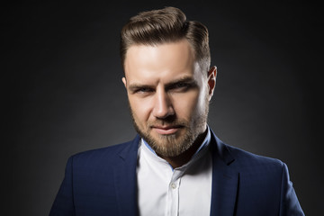 Portrait of young handsome male business man wearing suit. Perfect hair style and beard. Dark studio background