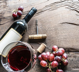 Wine glass, wine bottle and grapes on wooden background. Wine tasting. - 196982212