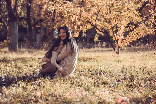 Fridge magnet Beautiful young woman and her little kid relaxing in autumn garden.