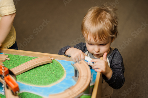 Cute little boy is playing with the toy wooden train