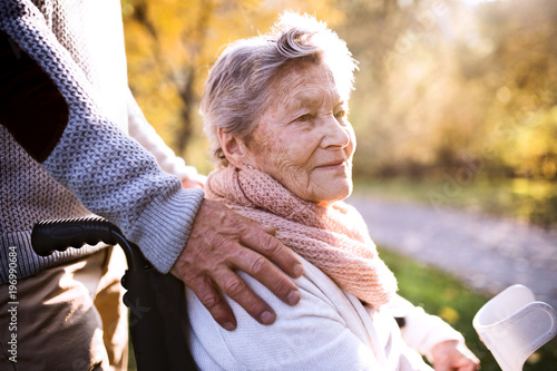 Senior man and woman in wheelchair in autumn nature.