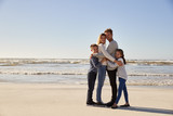 Portrait Of Loving Family Embracing On Winter Beach