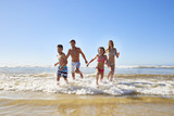 Family On Summer Beach Vacation Run Out Of Sea Towards Camera