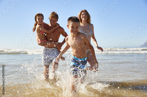 Family On Summer Beach Vacation Run Out Of Sea Towards Camera - 196998412