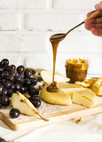 Honey flows from spoon in cheese on wooden Board with fruits