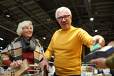 Portrait of happy senior couple buying groceries in supermarket paying with NFC payment via smartphone - 197004223