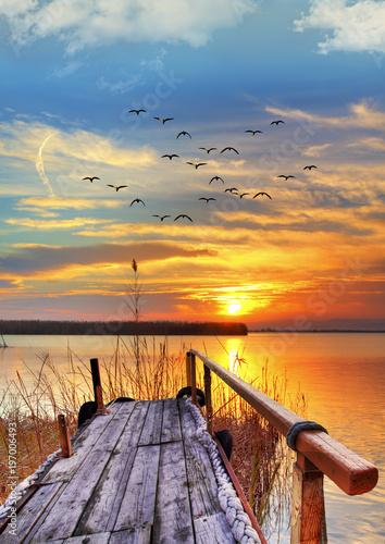 Foto op Plexiglas Oranje eclat embarcadero en el lago bajo el atardecer