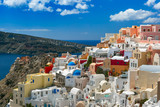 Picturesque view of white houses and church with blue domes in Oia or Ia, island Santorini, Greece - 197008458