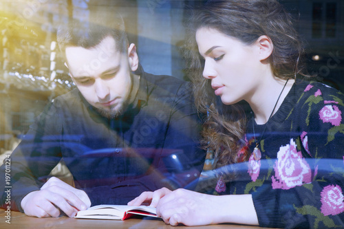 Loving couple reading a book in a cafe, view through a window. (Training, students, knowledge, exam concept)