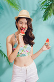 Portrait happy young asian woman is holding slice of watermelon over blue background