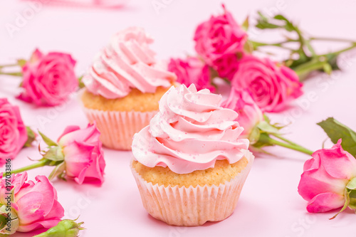 Cupcake with pink cream decoration and roses on pink pastel background. - 197033816