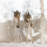 Red squirrels standing on horses in the snow