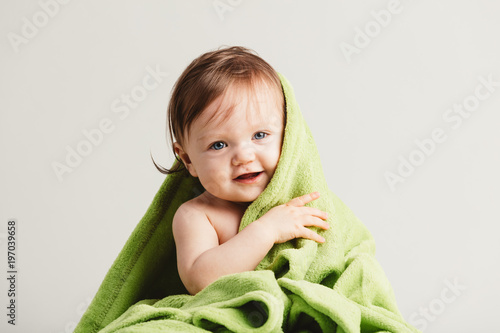 Cute little baby leaning out of cozy green blanket.