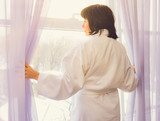 brunette middle-aged woman at the window at dawn wins sunlight
