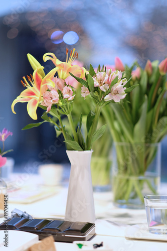 Fototapeta Bouquets of lilies and tulips in glass vases on a table